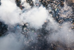 Garbage and fire burn in landfill. Also call trash, waste, rubbish. Destruction with combustion, heat, flame. Occurs smoke, toxic cause of air pollution, environmental damage and global warming.