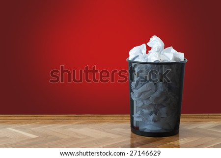 Garbage bin full of crumpled papers - stock photo