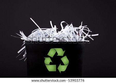 garbage bin with shredded paper and recycle symbol