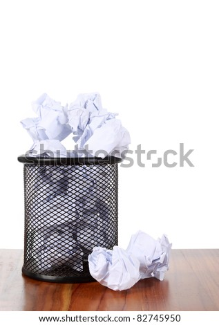 Garbage bin with waste paper on wooden surface