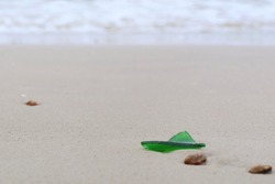 Garbage, broken glass bottle, on the beach with shells on sand in summer. Environment and nature concept.