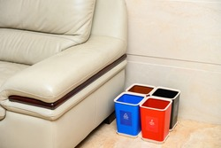 garbage classification bins near a sofa in a parlour at home English translation for the lables-blue means recyclable garbage,red means harmful,black means dry,brown means wet