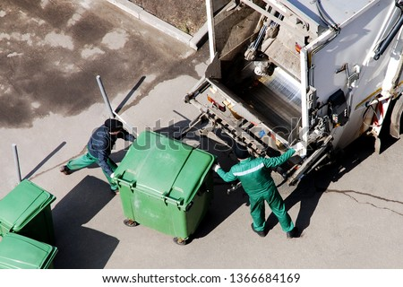 Garbage collection workers in residential area. Garbage truck that compresses garbage into mixed mass for burning. Separate garbage collection problem, household waste recycling. Stock photo ©