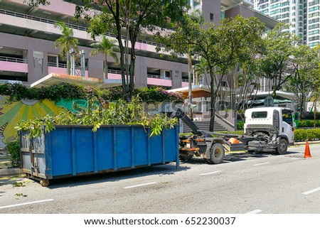 Garbage container bin latch with truck full of garden refuse, woods, chopped trees for disposal #652230037