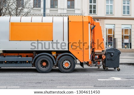 Garbage disposal lorry at city street. Waste dump truck on town road. Municipal and urban services. Waste management, disposal and recycling. Mock-up empty space. Copysapce for text