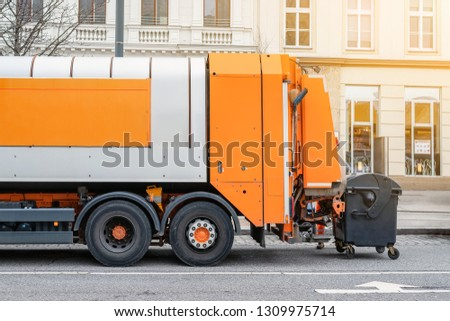 Garbage disposal lorry at city street. Waste dump truck on town road. Municipal and urban services. Waste management, disposal and recycling. Mock-up empty space. Copysapce for text.