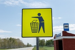 Garbage disposal. Yellow trash can sign at the bus stop. Trash icon sign on yellow label, road signs