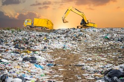 garbage dump pile in trash dump or landfill,backhoe and truck is dumping the gabage from municipal,garbage dump pile and dark sky background  ,pollution concept