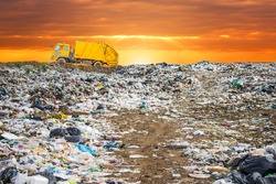 garbage dump pile in trash dump or landfill,backhoe and truck is dumping the gabage from municipal,garbage dump pile and sun set or sun rises sky background  ,pollution concept