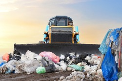 Garbage dump with plastic bags and food waste. Recycling of construction waste on junk yard. Refuse collection. Bulldozer dispose of rubbish at a landfill. Trash disposal area. Dozer on rubbish dump