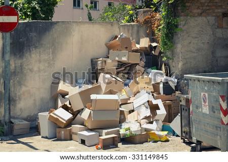 Garbage dumpsters cardboard boxes full of trash