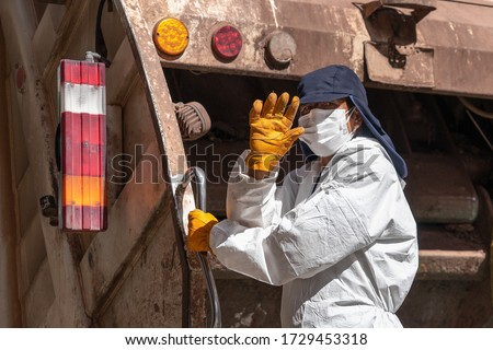 Garbage man in respiratory mask collects rubbish to garbage car in Cusco, Peru during coronavirus pandemic in Latin South America. Epidemic of coronavirus covid-19