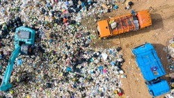 Garbage pile in trash dump or open landfill, Trash trucks dump waste products polluting in an trash dump, Surface and subsurface water contamination, modern hydraulic. Aerial top view