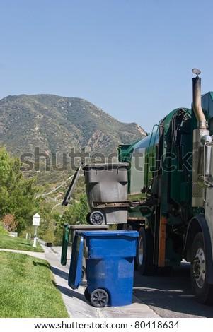 Garbage vehicle picks up a trash bin.