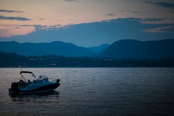 Garda Lake dusk, blue hour landscape, with a still speedboat and the hills in the background. Manerba del Garda, Lombardy, Italy.