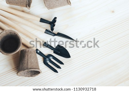 Garden accessories and pots for seedlings on a wooden background #1130932718