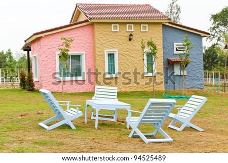 garden and home with white chairs and table on the grass