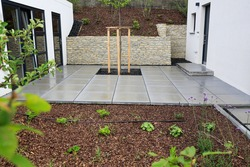 Garden and terrace design of a hillside plot with a modern mix of construction material as natural stone for walls or concrete paving slabs for pavement and beds with various foliage plants