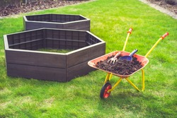 Garden barrow with soil and empty raised beds on grass prepared for filling with soil. Urban gardening concept.