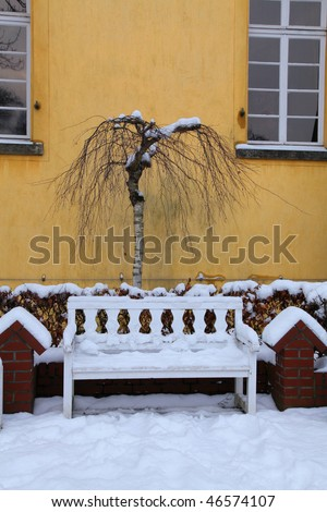 garden bench with snow in castle garden, germany