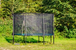 Garden big Trampoline on green grass in the yard. Outdoor Trampoline with safety net with Zipper entrance. Open Jump Trampolining.
