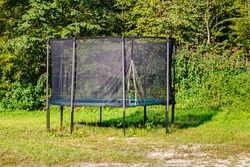 Garden big Trampoline on green Grass. Outdoor Trampoline with safety nets with Zipper entrance. Open Jump Trampolining.