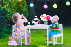 Garden birthday party for children. Kids outdoor celebration. Little boy and girl drinking tea and eating cake playing in the backyard in summer. Toddler and baby play with toy dishes and eat cupcakes
