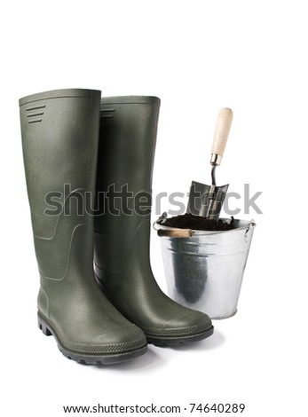 Garden boots and bucket with soil isolated on white