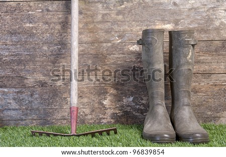garden boots and rake on grass against an old wooden wall