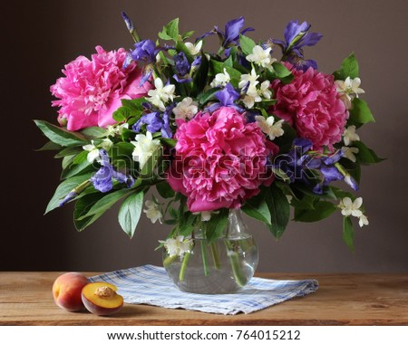 Garden bouquet of peonies, irises and Jasmine in a glass jug. Still life with flowers in a vase. #764015212
