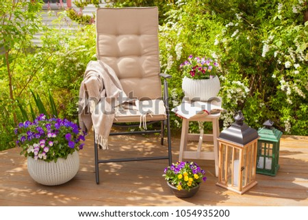 garden chair on terrace and pansy flowers #1054935200