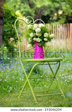 Garden chair with flowers in a romantic garden