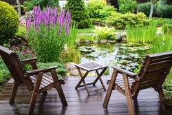 Garden chairs near the pond in a beautiful garden