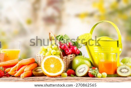 Garden concept, fresh fruits and vegetables on wooden table, watering can, seeds, plants
