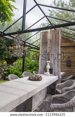 Garden design with concrete table with rooftop of a green house #1113986225