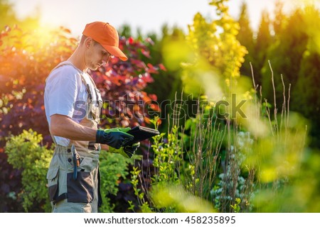 Garden Design with Tablet Device. Professional Gardener with His Tablet Computer. #458235895