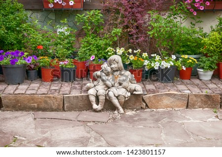 garden figures of a boy and a girl with a dog on a background of flowers in pots