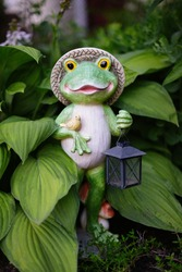 Garden figurine of a frog with lanterns in hand and a small bird. Garden figurine close-up among green leaves