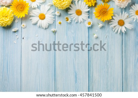 Photo of Garden flowers over blue wooden table background. Backdrop with copy space