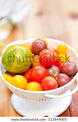 Garden fresh heirloom tomatoes in white colander