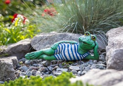 Garden frog lying among beautiful flowers, artificial toy