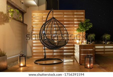 Garden Furniture Design. Starry Night Time in Stylish Backyard Garden with Wooden Porch with Wall and Planters Illuminated by Modern LED Lighting.