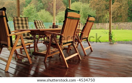 Garden furniture on a wet wooden floor.