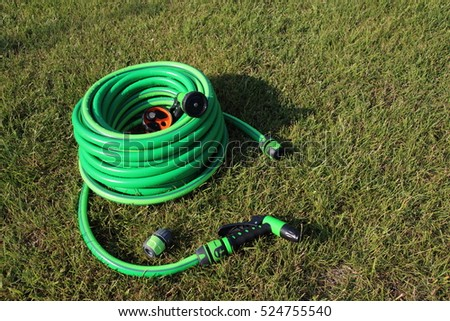 Garden hose bundle, connector and various adjustable showers (spray) on the mown lawn in the summer garden #524755540