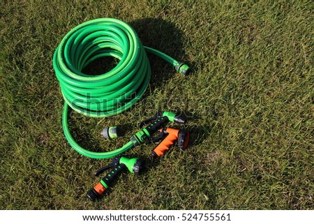 Garden hose bundle, connector and various adjustable showers (spray) on the mown lawn in the summer garden #524755561