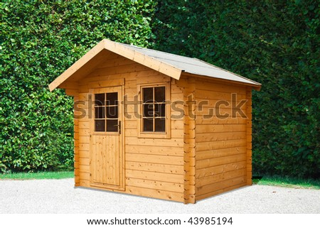 Garden house on the background of a living, evergreen hedge.
