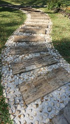 Garden landscaping of walk way or pathway made up of slab of tiled stones and pebbles. White pebbles and stones walkway decoration with circular tiles or carved rocks.