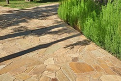 Garden landscaping with Pavement from Tiled Limestone Slabs. Backyard Garden Shaded Footpath from Tiled Stone Slabs. Flagstone Walkway in The Garden. Shady Pathway From Stone Tiles In The Park.