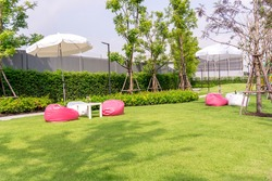 Garden of smooth green grass lawn with white and pink beanbag under white umbrella, trees, shrub, in a good maintenance landscaped backyard of the park