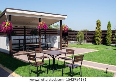 Garden Or Backyard Outdoor Pavilion With Wood Pergola, Bar Counter, Brick Oven, Fireplace And Barbecue For Cookout Food. Summer Party Place. Green backyard